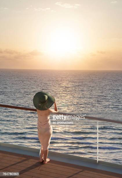 caucasian woman on boat admiring sunset - railing stock pictures, royalty-free photos & images