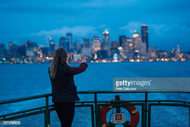 caucasian woman on boat photographing urban waterfront with cell phone - 旅客船 ストックフォトと画像