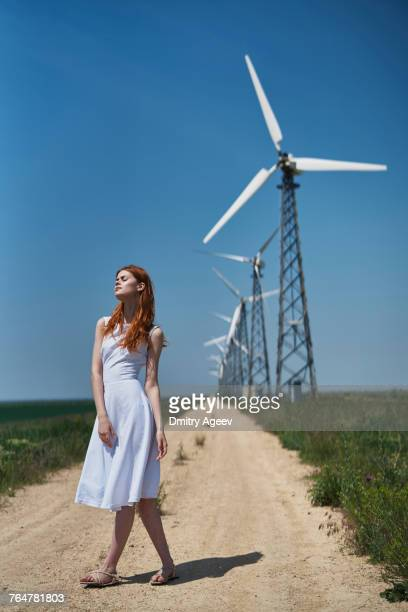 Caucasian woman on dirt path near wind turbines
