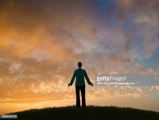 Caucasian woman on hill admiring sunset on clouds