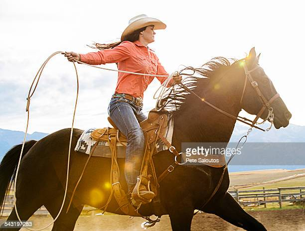 Caucasian woman on horse throwing lasso at rodeo