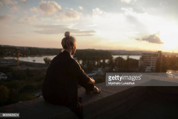 caucasian woman on roof admiring scenic view of sunset - admiration stock pictures, royalty-free photos & images