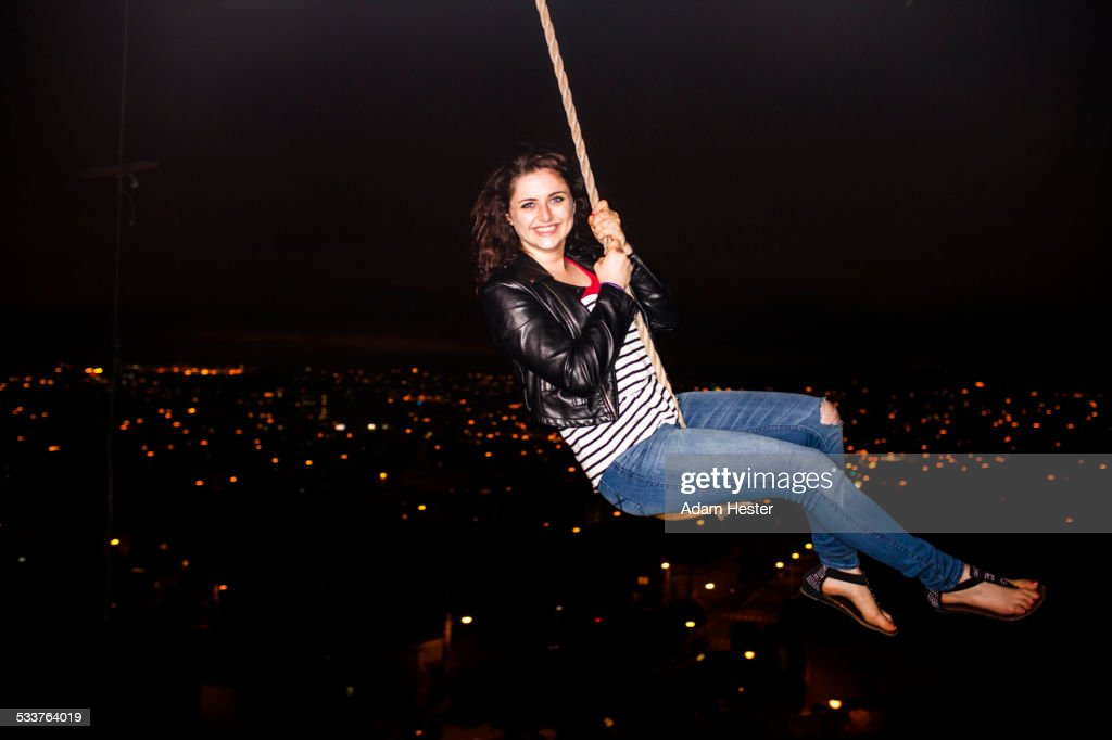 Caucasian woman on rope swinging over scenic view of cityscape : Foto stock
