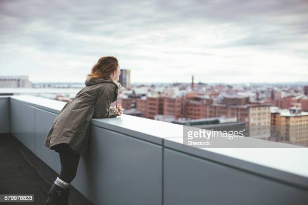 caucasian woman on urban rooftop admiring cityscape - railing stock photos and pictures