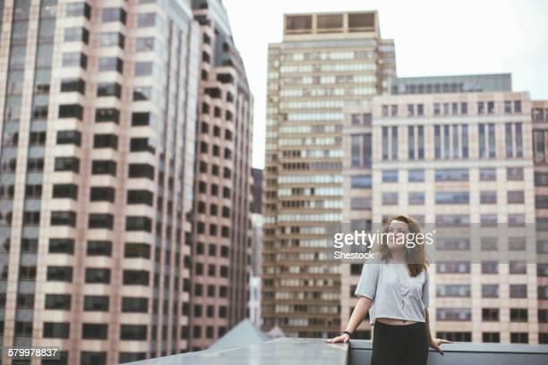 Caucasian woman on urban rooftop admiring cityscape
