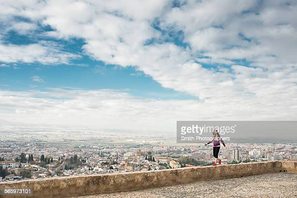 Caucasian woman on wall overlooking scenic view of cityscape, Granada, Spain
