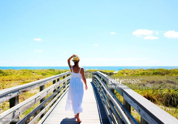 caucasian woman on wooden walkway to beach - florida nature stock pictures, royalty-free photos & images