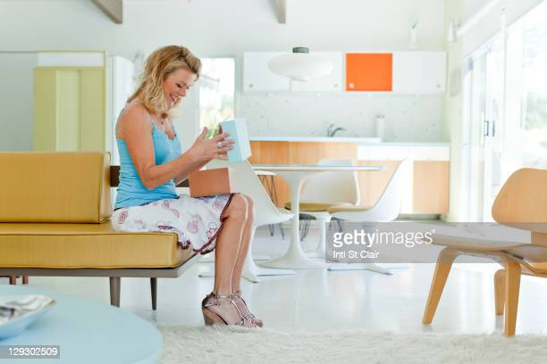 Caucasian woman opening box in living room