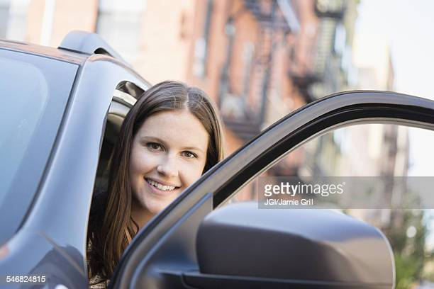 Caucasian woman opening car door
