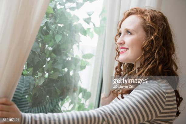 Caucasian woman opening curtains at window