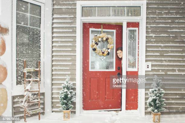 Caucasian woman opening door to snow