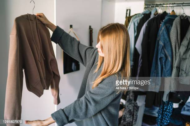 caucasian woman organizing closet at home,spain - clothing stock pictures, royalty-free photos & images