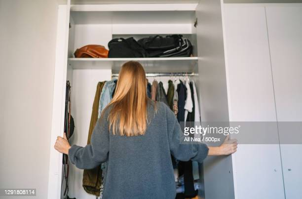 caucasian woman organizing closet at home,spain - order stock pictures, royalty-free photos & images