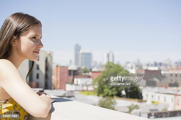 Caucasian woman overlooking cityscape from urban rooftop