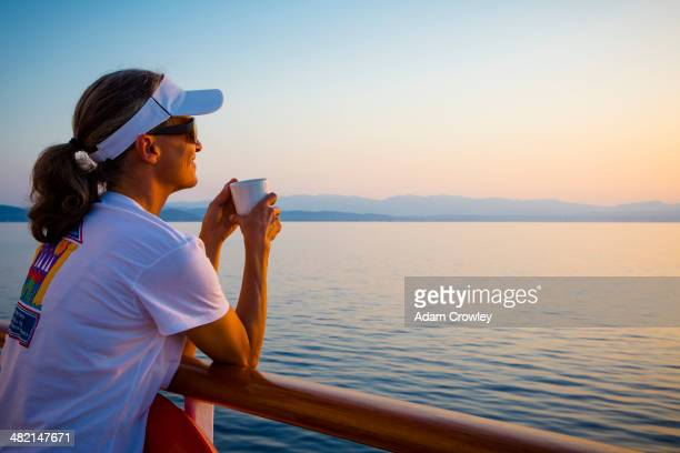 caucasian woman overlooking ocean from boat deck - 乗り物に乗って ストックフォトと画像