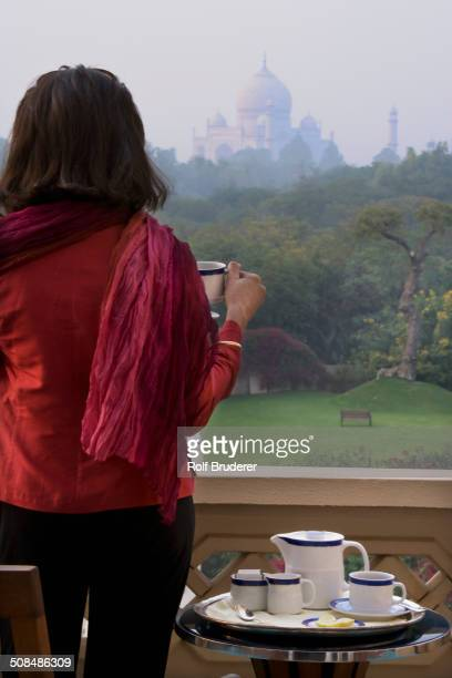 Caucasian woman overlooking Taj Mahal from balcony, Agra, India