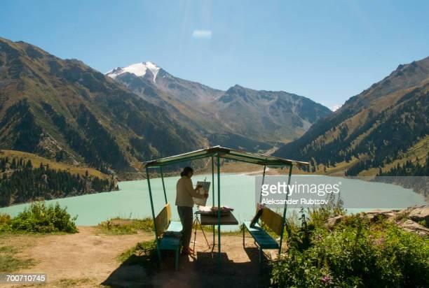 Caucasian woman painting mountain landscape