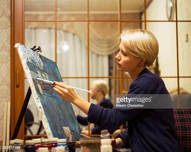 Caucasian woman painting on canvas near mirror