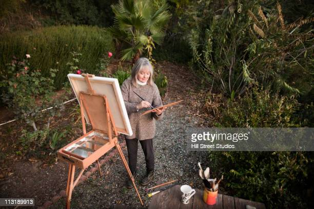 Caucasian woman painting on easel outdoors