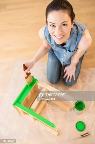 Caucasian woman painting stool