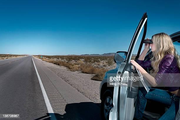 Caucasian woman parked on roadside using binoculars