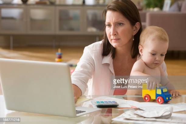 Caucasian woman paying bills on computer with son on lap