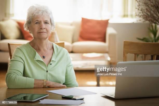 Caucasian woman paying bills on laptop