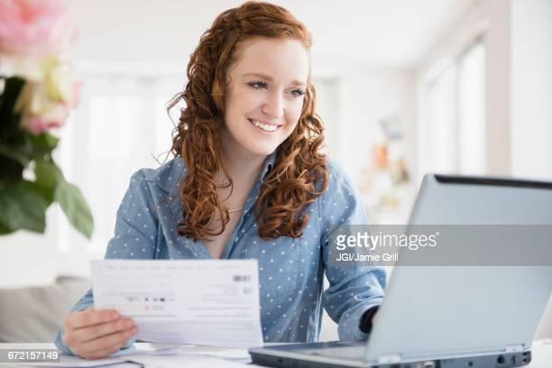 Caucasian woman paying bills using laptop