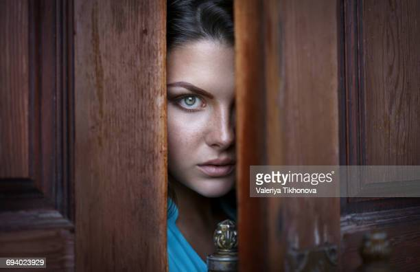 Caucasian woman peeking in doorway