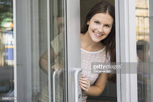 Caucasian woman peeking out doorway