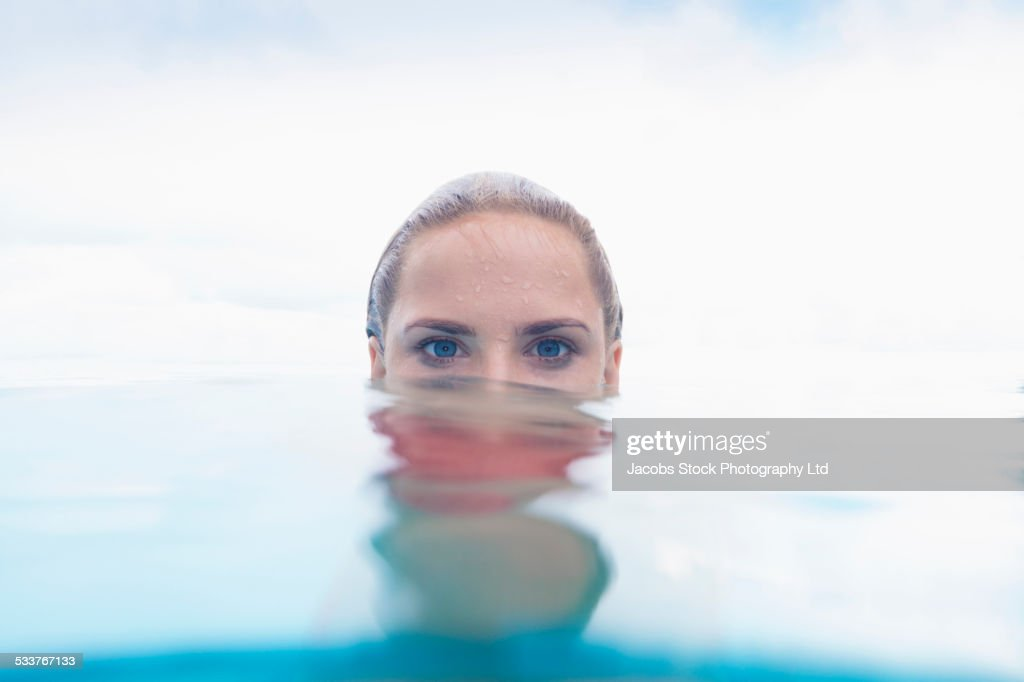 Caucasian woman peering over swimming pool water surface : Foto stock