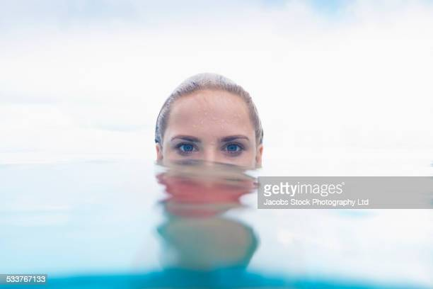 Caucasian woman peering over swimming pool water surface