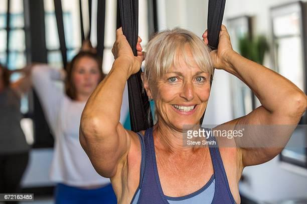 Caucasian woman performing yoga hanging from silks