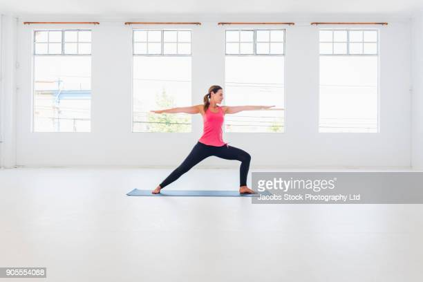 caucasian woman performing yoga stretching arms - yoga studio stock pictures, royalty-free photos & images