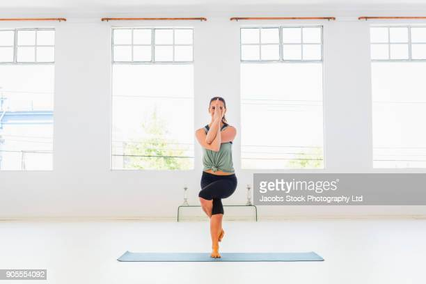 caucasian woman performing yoga twisting arms and legs - twisted stock pictures, royalty-free photos & images