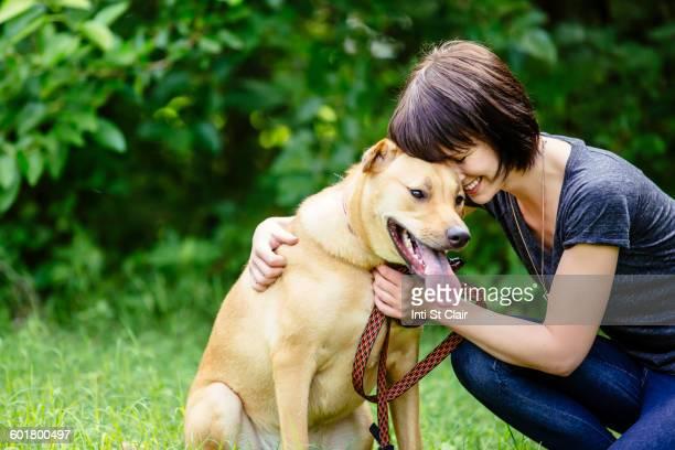 Caucasian woman petting dog in field