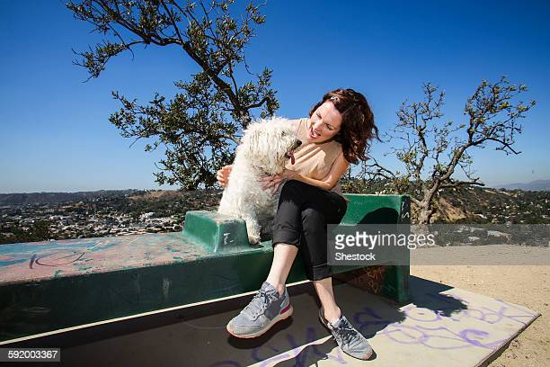Caucasian woman petting dog on hilltop bench