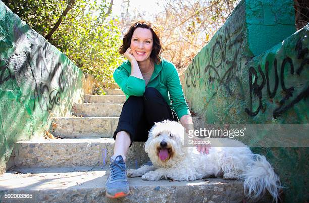 Caucasian woman petting dog on staircase with graffiti