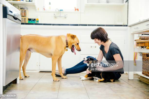 Caucasian woman petting dogs in kitchen