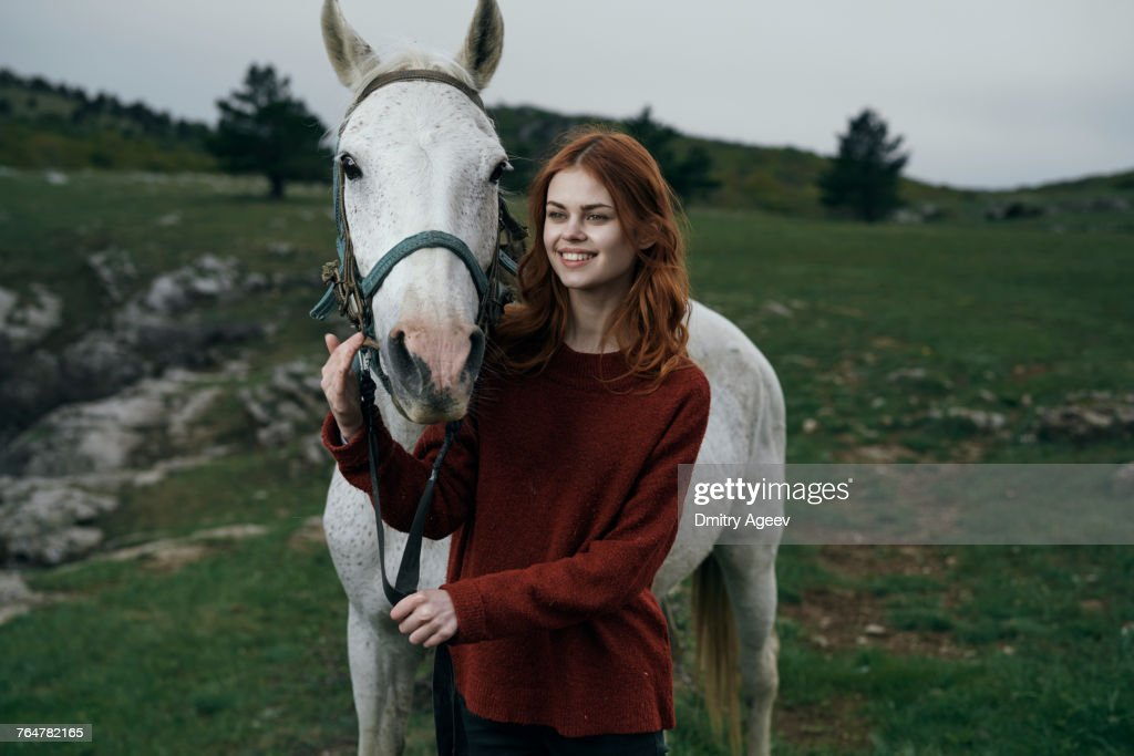 Caucasian woman petting horse : Stock Photo
