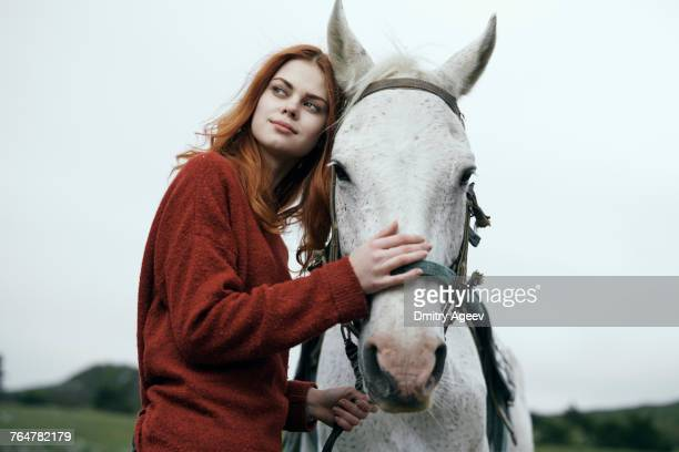 caucasian woman petting horse - dressage horse russia stock photos and pictures