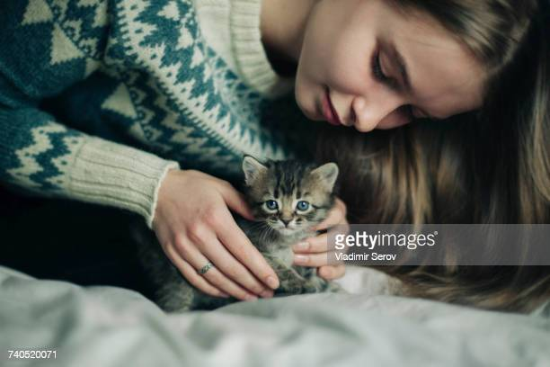 Caucasian woman petting kitten