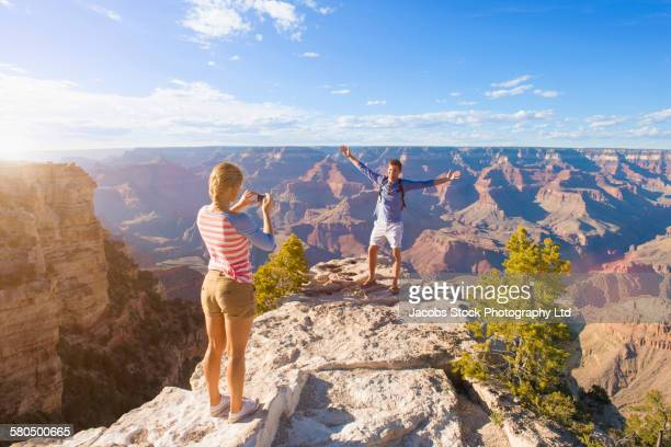 caucasian woman photographing boyfriend in desert landscape, grand canyon, arizona, united states - category:grand_canyon_national_park stock pictures, royalty-free photos & images