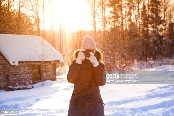 Caucasian woman photographing in snow
