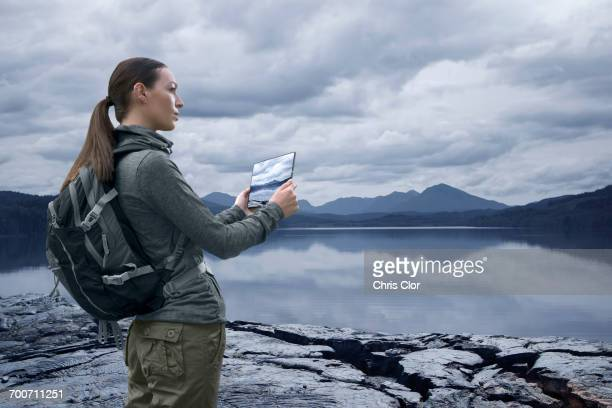 Caucasian woman photographing mountain lake with digital tablet