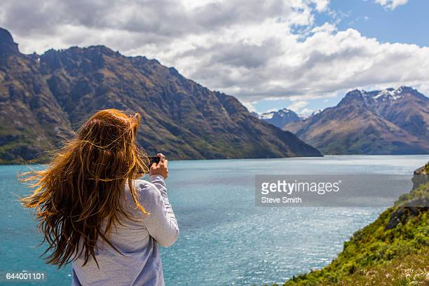 caucasian woman photographing mountains and lake, queenstown, otago, new zealand - lake auburn stock photos and pictures