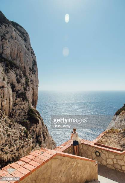 Caucasian woman photographing ocean near staircase