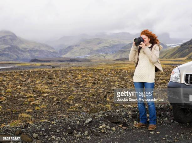 Caucasian woman photographing on remote road