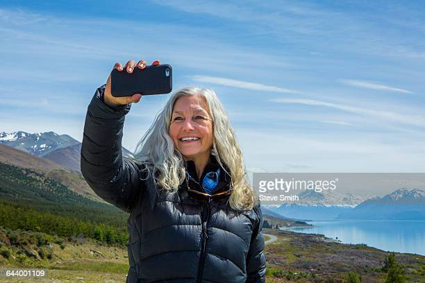 Caucasian woman photographing remote landscape