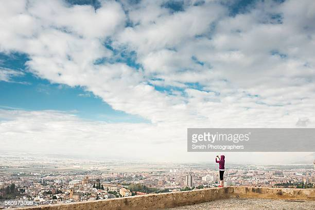 Caucasian woman photographing scenic view of cityscape, Granada, Spain